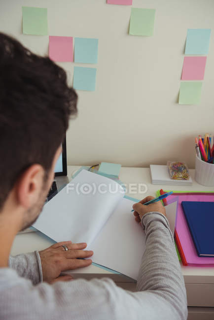 Rear view of man writing on document while sitting at desk — Stock Photo