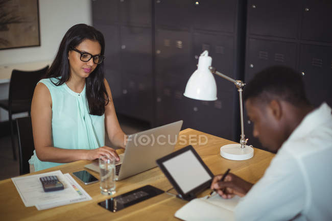 Businessman and a colleague working at their desk in office — Stock Photo