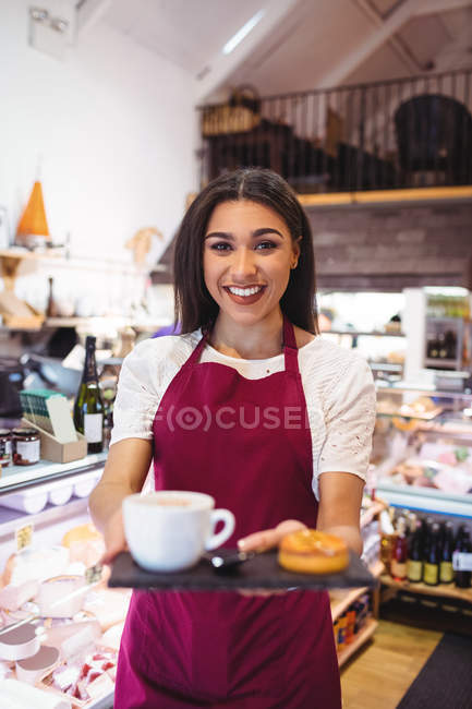 Portrait of smiling waitress holding a cup of coffee and snacks in super market — Stock Photo