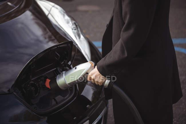 Section médiane de l'homme recharge voiture électrique à charge conductive pour véhicules électriques — Photo de stock