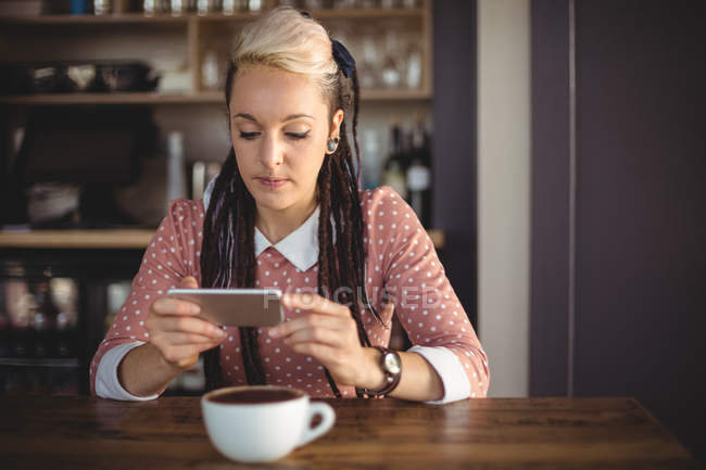 Woman using mobile phone in cafe — Stock Photo