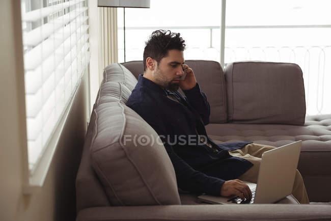 Uomo che parla sul cellulare mentre usa il computer portatile sul divano di casa — Foto stock