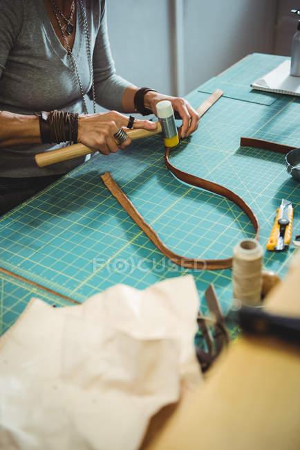 Meados de seção de artesã martelando couro na oficina — Fotografia de Stock