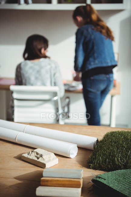 Rolled-up document and blueprint with stone slab on table in office — Stock Photo