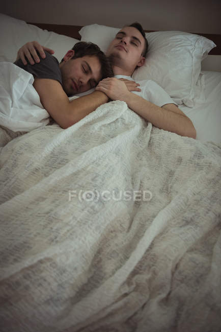 Gay couple embracing while sleeping on bed in bedroom — Stock Photo