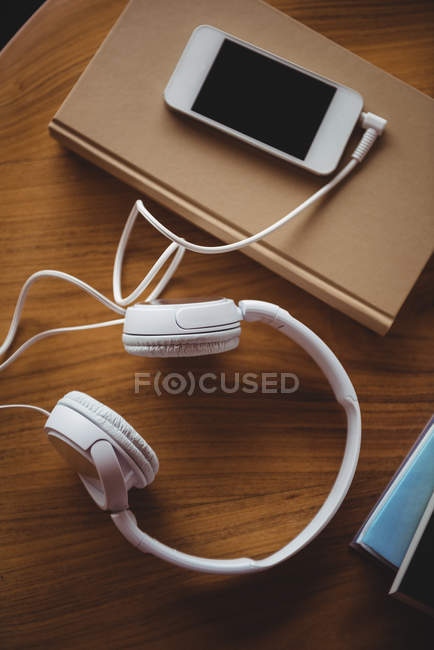 Headphones, mobile phone and book on wooden table at home — Stock Photo