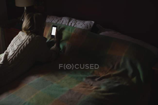 Frau lag und benutzte Handy auf Bett im Schlafzimmer — Stockfoto