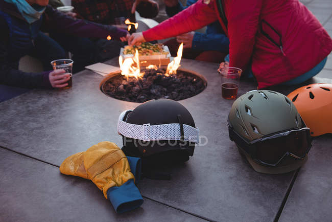 Group of skiers sitting at fire place in ski resort — стоковое фото