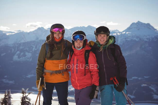 Три лыжниц, стоя вместе в снег покрыты горы — стоковое фото