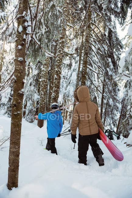 Rear view of couple with ski and snowboard walking on snowy mountain slope — Fotografia de Stock