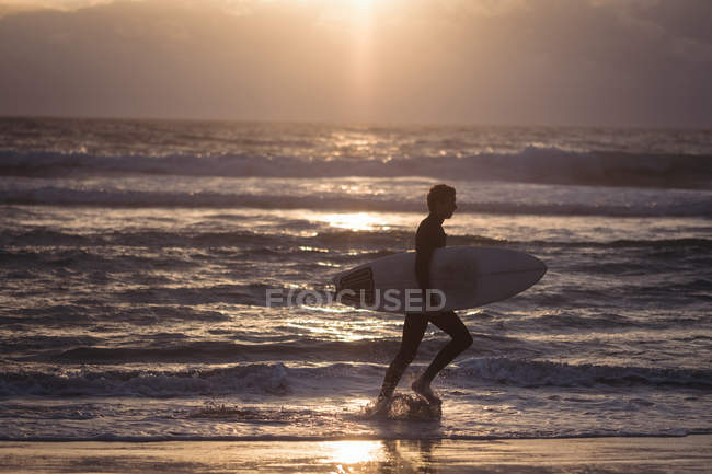 Silhouette of a man carrying surfboard walking on beach at dusk — Stock Photo
