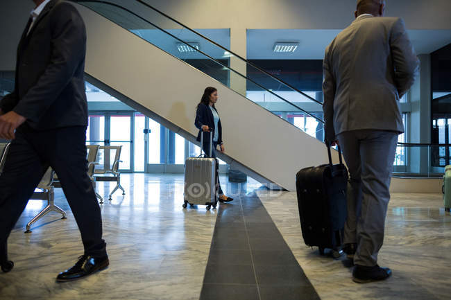 Business people walking with luggage in waiting area at airport — Stock Photo