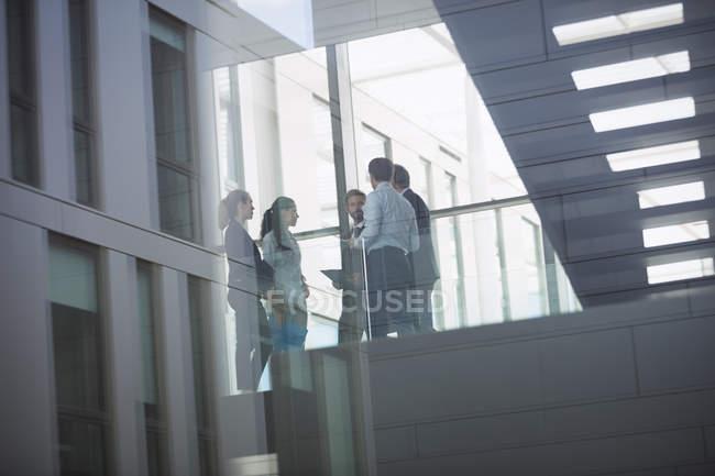 Група ділових людей, що взаємодіють в коридорі Офісна будівля — стокове фото
