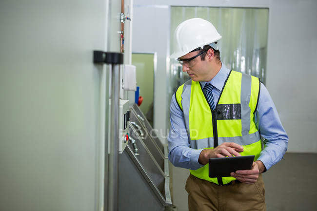 Technician examining machine at industrial factory — Stock Photo