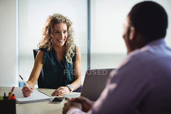 Businesswoman and businessman interacting with each other in office — Stock Photo