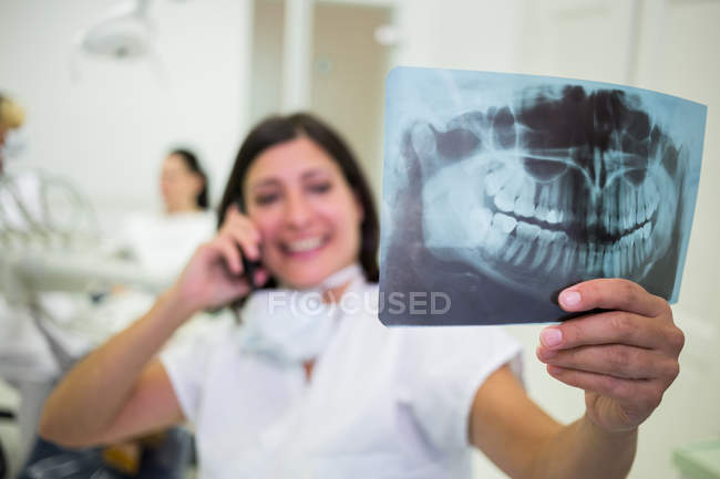 Dentist checking x-ray report while talking on mobile phone at aesthetic clinic — Stock Photo