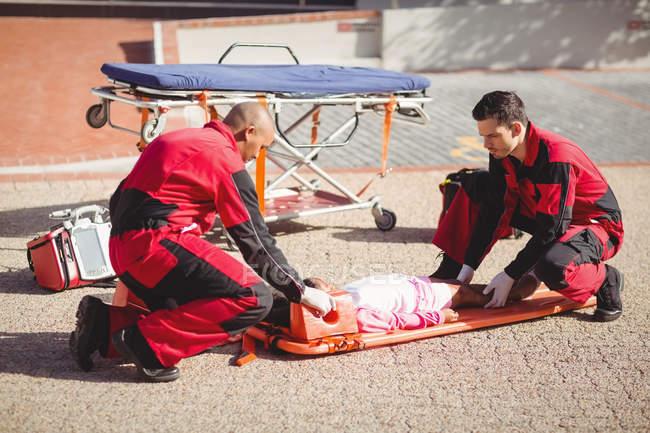 Paramédicos colocando menina ferida em um rodapé na rua — Fotografia de Stock