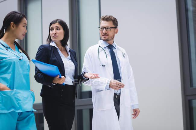 Врачи и медсестра взаимодействуют во время прогулки в помещении больницы — стоковое фото