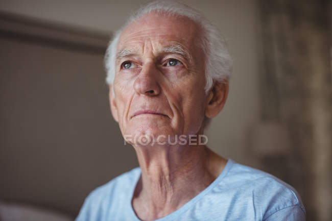 Thoughtful senior man in bedroom at home — Stock Photo