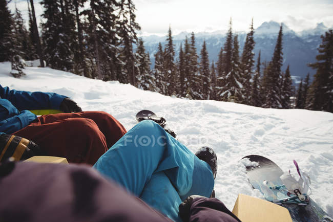 Low section of couple sitting at snow covered mountain - foto de stock