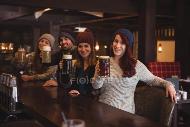 Ritratto di amici che tengono bicchieri di birra al bancone del bar — Foto stock