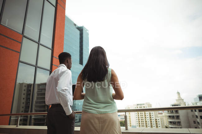 Vue arrière de l'homme d'affaires et un collègue debout au balcon du bureau — Photo de stock