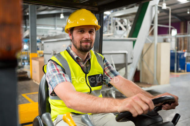 Portrait of young male worker driving forklift in warehouse — Stock Photo