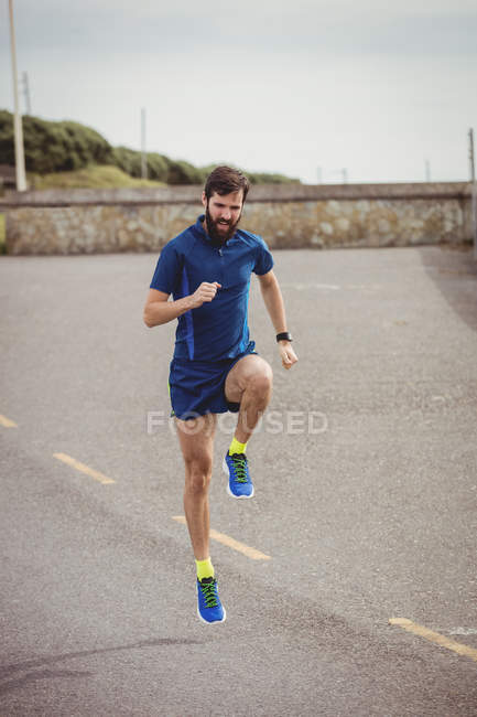 Handsome athlete running on country road — Stock Photo