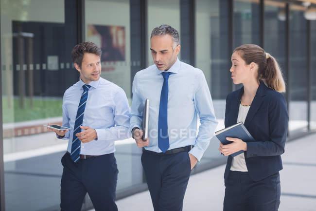 Homme d'affaires confiant marchant avec des collègues à l'extérieur du bureau — Photo de stock