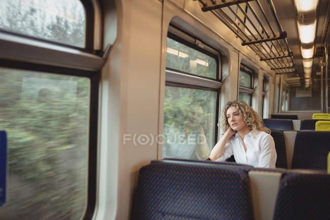 Продуманий бізнес-леді дивлячись через вікно під час подорожі — стокове фото