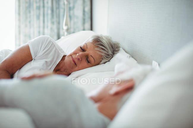 Старший пара спати на ліжку в спальні — стокове фото