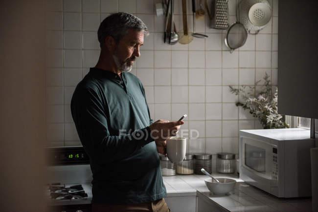 Людина, що використання мобільного телефону під час за чашкою кави в домашніх умовах — стокове фото