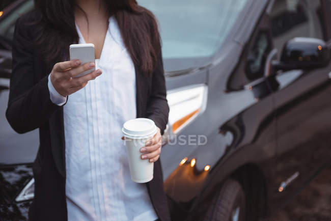 Woman standing next to car and using mobile phone at electric vehicle charging station — Stock Photo