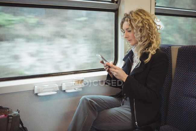 Focused businesswoman using smartphone while travelling — Stock Photo