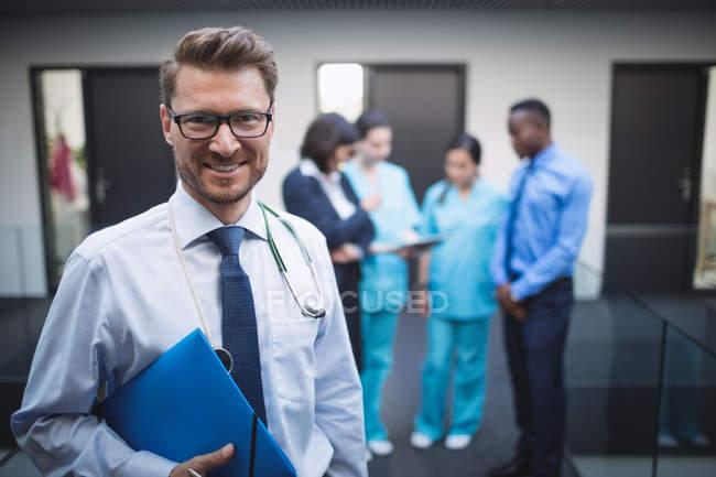 Портрет улыбающегося врача с медицинским заключением в больничном коридоре — стоковое фото