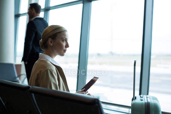 Thoughtful female commuter with passport and boarding pass in waiting area at airport — Stock Photo