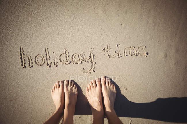 Sección baja de la mujer de pie cerca del tiempo de vacaciones dibujado en la playa de arena - foto de stock