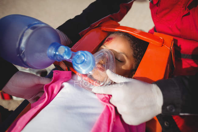 Paramedic giving oxygen to injured girl at accident spot — Stock Photo