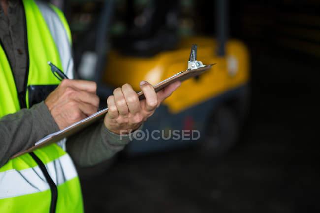 Trabajador de sexo masculino en el portapapeles en el almacén - foto de stock