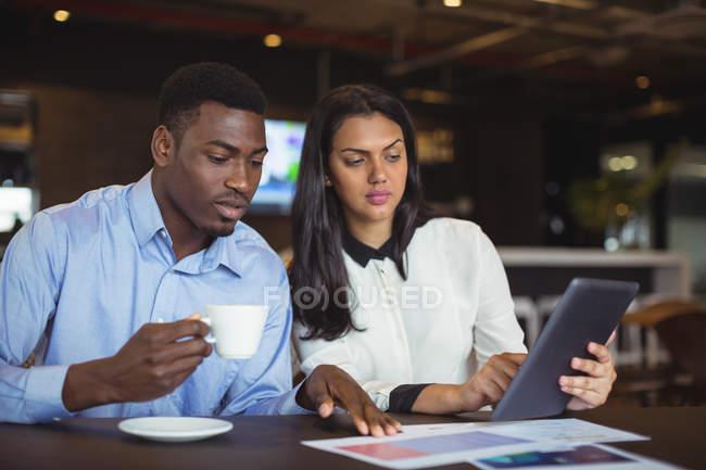 Homme d'affaires et un collègue discutant sur tablette numérique au bureau — Photo de stock
