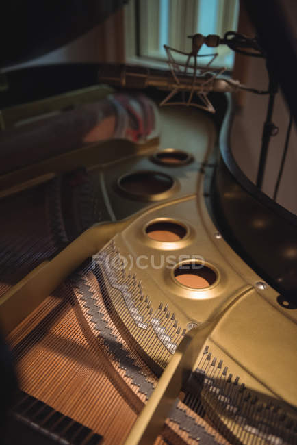 Piano cast iron plate and strings in recording studio — Stock Photo