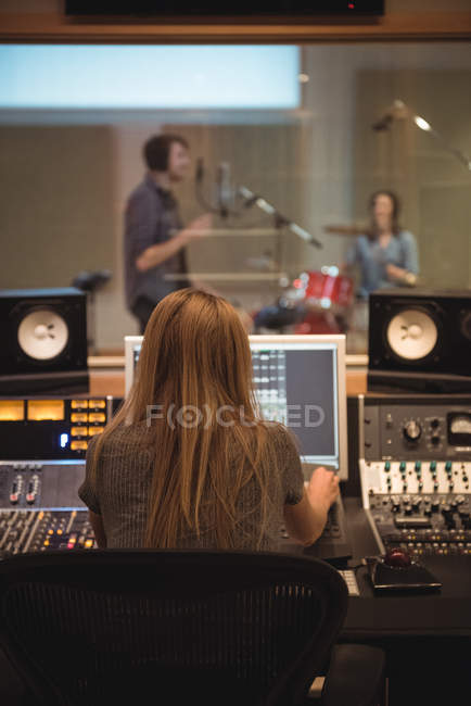 Rear view of audio engineer using sound mixer in recording studio — Stock Photo
