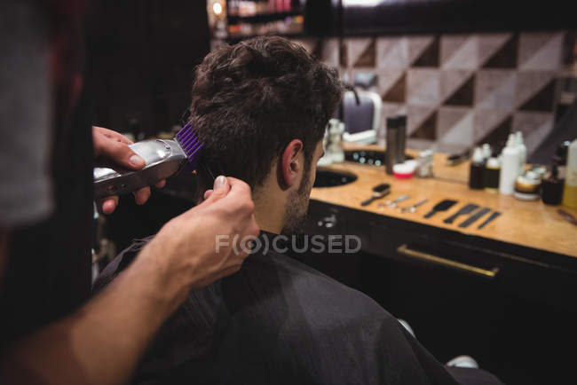 Man getting hair trimmed by stylist with trimmer in barber shop — Stock Photo