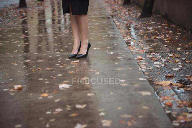 Pés em sapatos elegantes de mulher de negócios na passarela pedestre molhada — Fotografia de Stock