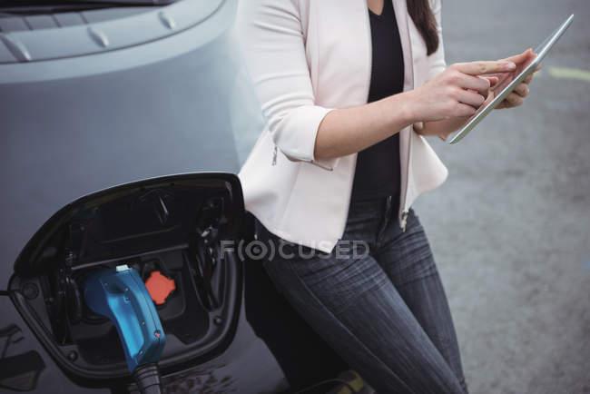 Section médiane de la femme à l'aide de tablette numérique lors du chargement de la voiture électrique sur la rue — Photo de stock