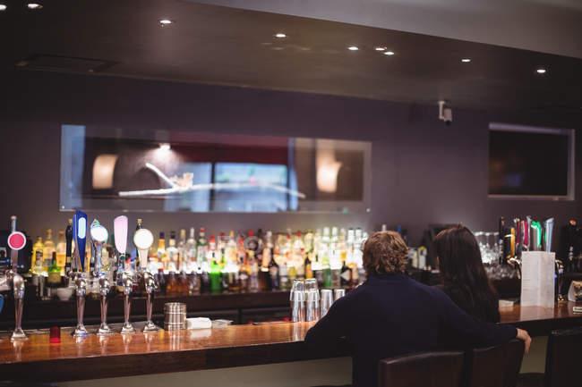 Задній вид на пару сплячих напої разом в бар — стокове фото
