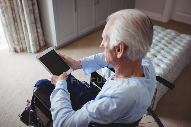 Senior man sitting on wheelchair and using digital tablet at home — Stock Photo