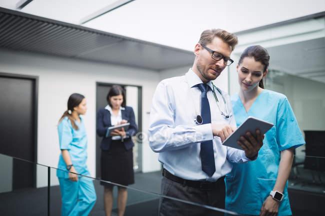 Médico e enfermeira discutindo sobre tablet digital no corredor do hospital — Fotografia de Stock
