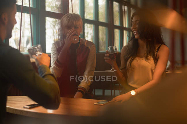 Cheerful friends enjoying drinks in bar interior — Stock Photo
