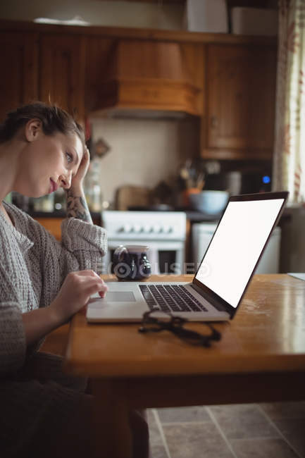 Tensed woman using laptop on table in kitchen at home — Stock Photo